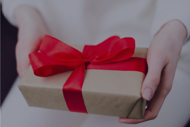 Woman holding a wrapped gift.